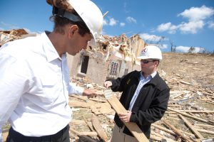 two men wearing hard hats examine a piece of wood in a debris field from the April 27, 2011 tornado