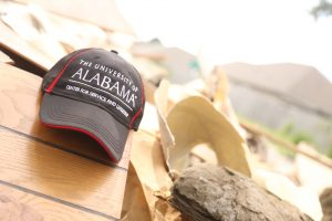 """a ball cap hat reading """"The University of Alabama Center for Service and Leadership"""" sits on top of a pile of debris at a volunteer work site."""