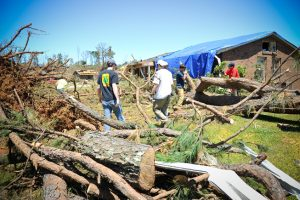 Debris from felled trees sits in the foreground with people working to remove them from around a home with a blue tarp on the roof.