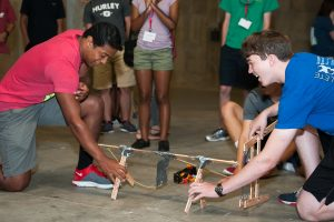 Two students holding a small catapult that was built during a summer camp