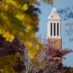 The top of Denny Chimes seen through trees.