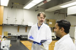 Two scientists in white coats discuss research in a lab.