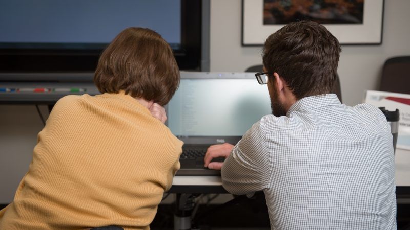 Two people working on a computer project.