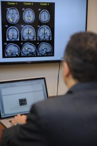 Man sits at a desk looking at brain images