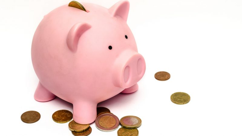 A piggy bank with pennies scattered around it.