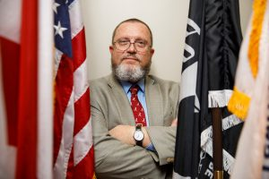 A professor studying veteran suicides stands amidst the U.S. and military flags.