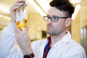 Dr. Lukasz Ciesla looks at a plant extract in a jar.