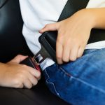 A person buckles a seat belt inside a vehicle.
