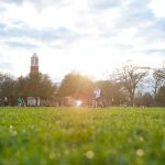 The sun shines onto grass on The University of Alabama campus.