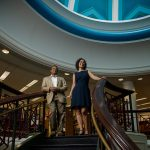 Business professors stand atop spiral staircase.