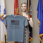 A female college student holds a T-shirt related to her non-profit organization