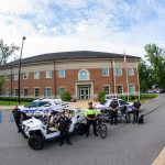 University police officers standing in front of the UA Police Center with patrol cars, bicycles and a police dog.