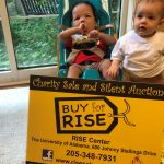 Two young children with signage promoting the RISE fundraiser.