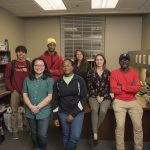 University students pose for a picture in an office filled with independent living supplies