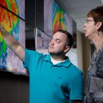A meteorlogist points to a large screen displaying weather radar information while another scientist looks on.
