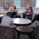 Members of the University of Alabama and Auburn University talk around a table