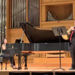 Matthew Meadows performs on a stage on the French horn with a pianist.