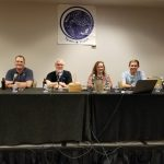 A panel of scientists sit at a table ready to talk about space.