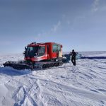 A red, tracked vehicle pulls a large, flat antenna across the white, Antarctic ice.