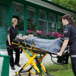 Two female paramedics escort a patient on a stretcher out of a home