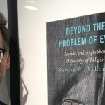 Dr. Nathan Loewen beside a photo of his book.