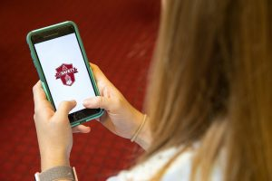 A student looking at the UA Safety app on a smartphone.