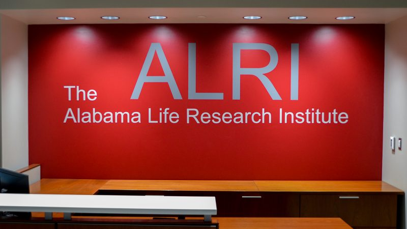 The name of the Alabama Life Research Institute in silver on a red wall.