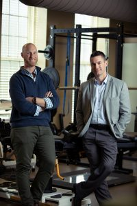 Two UA professors pose for a photo in an exercise lab.