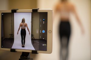 A woman in work-out clothes stands still while a tablet computer captures an image of her, shown on screen.