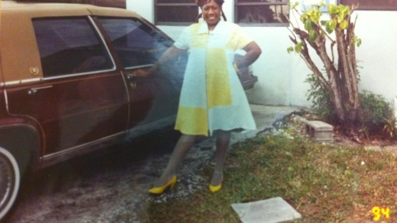 Green's mother in yellow dress and shoes in front of their home.