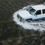 A pickup truck drives through a flooded street.