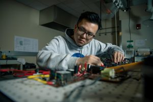 A student works with electronic equipment in a lab.