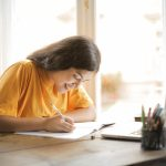 woman-in-yellow-shirt-writing-on-white-paper