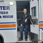 A EMT poses for a photo in the door of an ambulance.