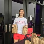 Abigail Gunter passing out bags of free breakfast and lunch to Tuscaloosa City School students