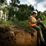 A researcher in safety gear sits on the edge of a hole in the forest taking notes.