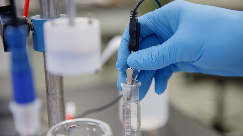 A blue-gloved hand works on a lab bench inserting materials in a beaker.