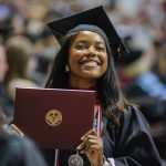 Woman smiles with her degree in hand.