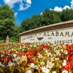 The University of Alabama entrance marker is pictured with flowers in front.