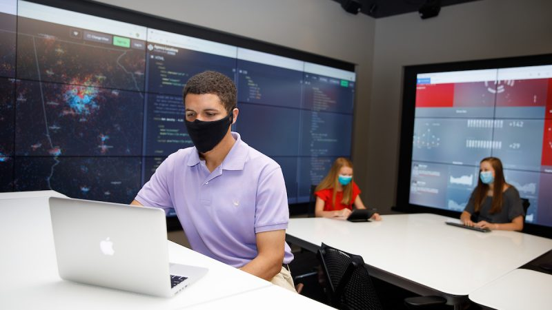 Three students in a lab wearing face masks.