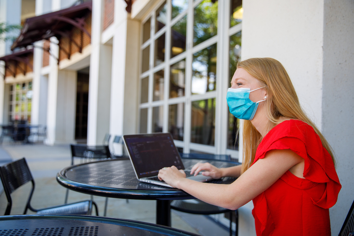 Female student wearing mask sits at an outdoor table working on a laptop