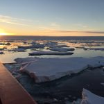 The sun sits on the horizon above the ice-laden sea off the coast of Antarctica.