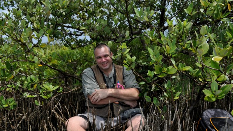 Man poses for photo in wetlands.