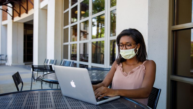 A woman wearing a face mask uses a lap top at a patio table at The University of Alabama