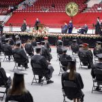 Students sit in cap and gown at commencement ceremony.