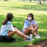 Two females with masks sit on the campus lawn.