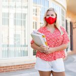 A student wearing a red mask that matches her shirt.
