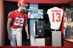 A display inside the Bryant Museum features a manikin wearing a University of Alabama football uniform, a trophy from the College Football Playoff and Tua Tagovailoa's jersey.