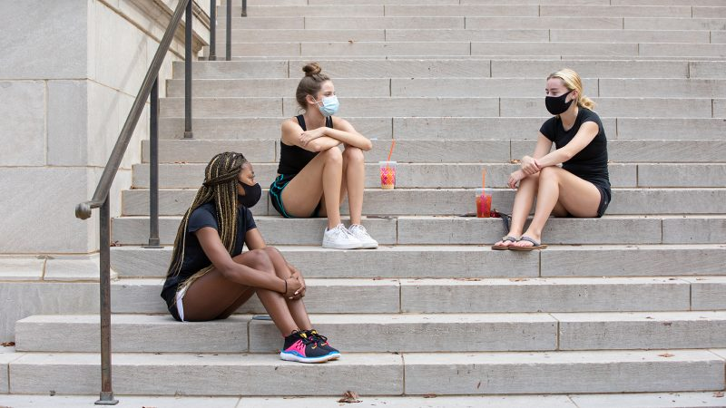 three female students sit on the steps of Gorgas Library talking