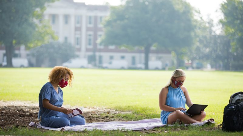 Two female students in masks sit on the UA campus lawn.